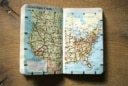 United_states_Canada_map_book_on_wood_table
